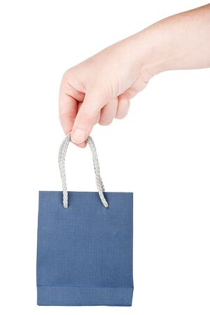 Female hand holding little blue gift bag isolated on white photo