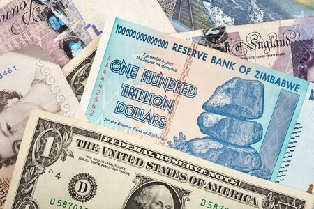 currency exchange: Money background with US dollars, British pounds, Lithuanian litas and Zimbabwe hundred trillion dollars