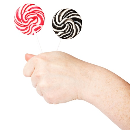 Hand holding two spiral lollipops isolated on white background   photo
