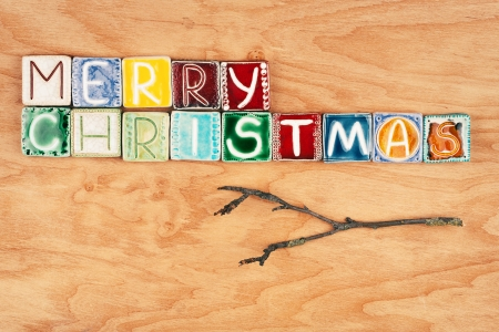 Words merry christmas made from ceramic letters on wood texture photo