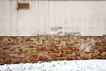 Detail of the old wall and a ground covered with snow   photo