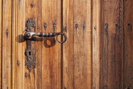 Ancient rusty church door handle on brown old wooden door   photo