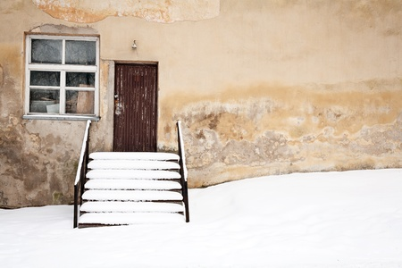 Old wall with window and stairs and a ground covered with snow