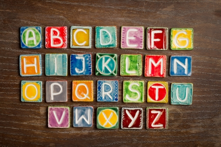 Colorful handmade ceramic alphabet on wood texture photo