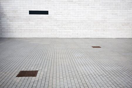 Tiled wall with a blank white bricks and paving photo