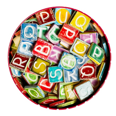 Tin full of colorful handmade ceramic letters isolated on white photo