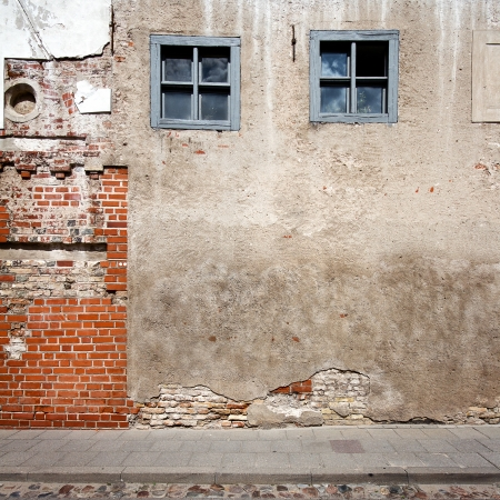 the red wall: Aged weathered street wall with some windows Stock Photo
