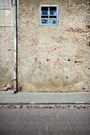 Aged weathered street wall with small window photo