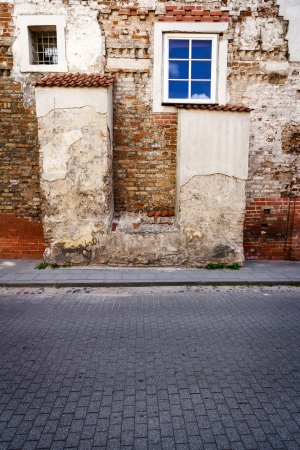 Aged weathered street wall with some windows photo