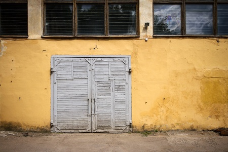 Old wooden gate in grungy yellow wall photo