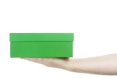 Female hand holding cardboard box isolated on white background photo