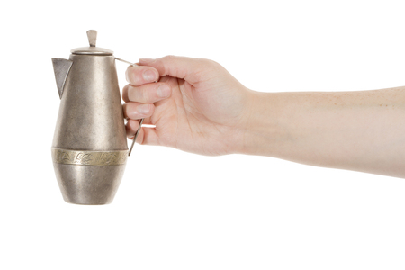 Hand holding silver jug isolated over white background photo