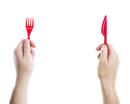 eating right: Red disposable knife and fork in hands isolated on white background    Stock Photo
