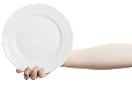 Female hand holding big white plate isolated on white background photo