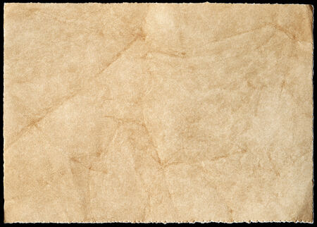 Old stained paper isolated on a black background.  photo