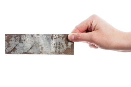 Hand holding old metal plate isolated on white photo