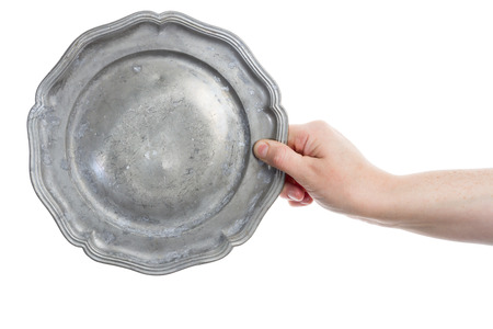 pewter: Female hand holding old pewter plate isolated on white background  Stock Photo