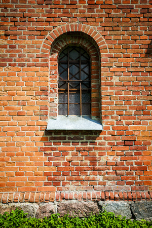 Red brick wall with a window photo