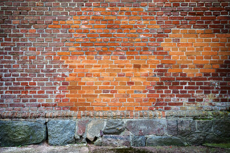 Red brick wall background with stone basement photo