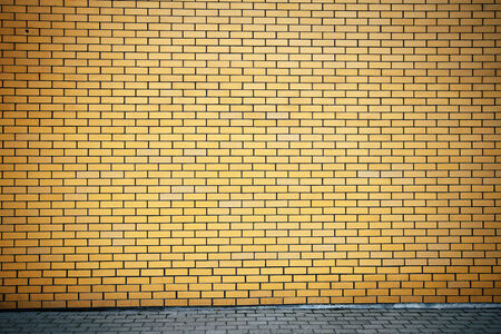 Modern vibrant yellow brick wall as a image with vignette  photo