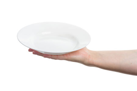 Female hand holding big white plate isolated on white
