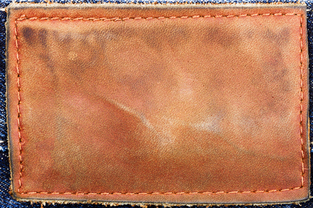 leather stitch: Blank leather jeans label sewed on a blue jeans Stock Photo