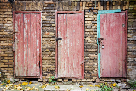 Three old wooden plank doors in a wall photo