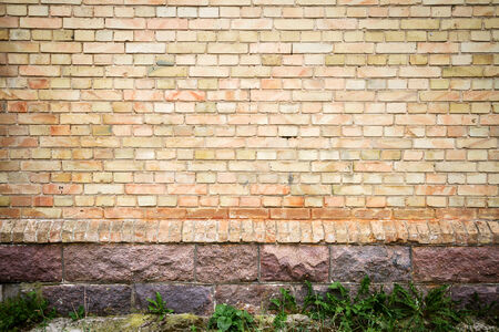 Yellow brick wall background with stone basement photo