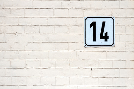 number 14: Number 14 on textured brick wall