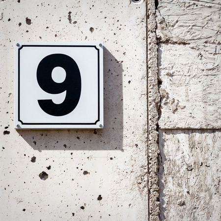 Number 9 on textured concrete wall