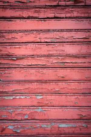 Peeling red paint on weathered wood texture photo