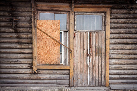 boarded: Boarded up windows and old door of a abandoned house