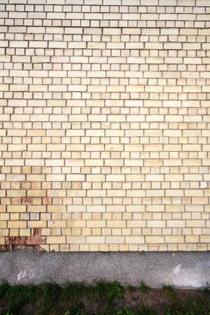Yellow brick wall background with stone basement photo