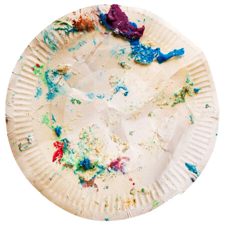 Crumpled disposable paper plate with cake crumbs isolated on white background. End of birthday party concept. Imagens