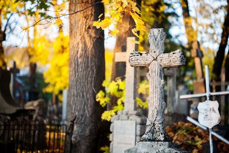 A cross monument in a cemetery on sunny autumn day