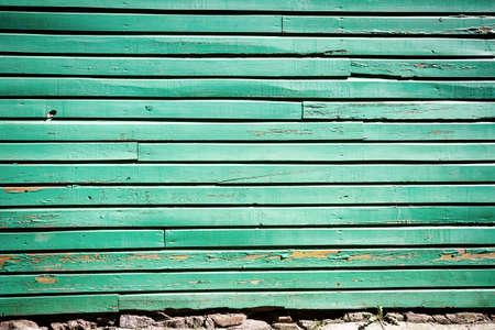 Peeling green paint on weathered wood wall photo