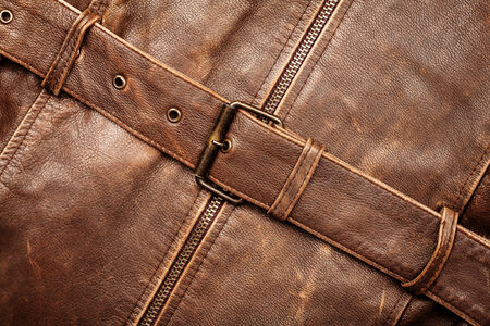Closeup of a leather texture with a belt and zipper photo