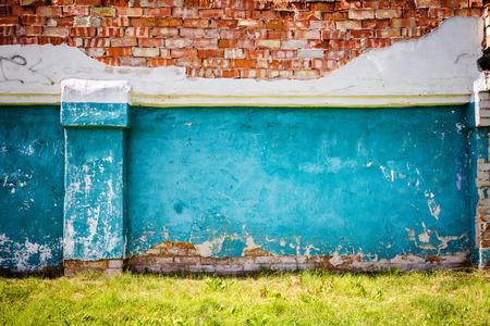 Oude blauwe bakstenen muur met groen gras