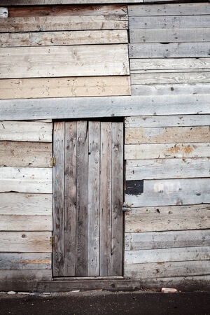 Old gray wooden plank door with padlock photo