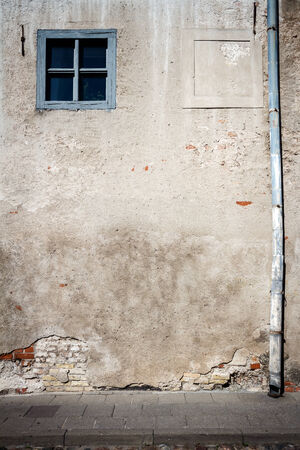 Aged weathered street wall with small window