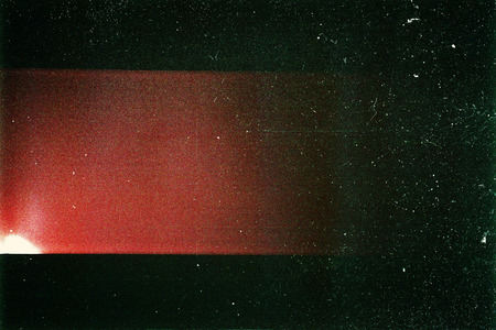 light red: Designed film texture background with heavy grain, dust and a light leak