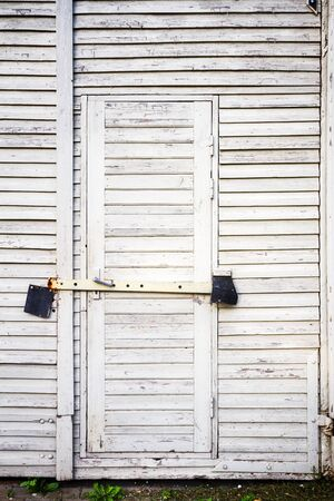 Old white wooden plank door with padlock photo
