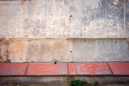 sill: Old cracked plaster wall with red tin sill Stock Photo