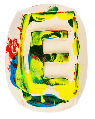 Handmade of white clay letter E painted with colorful acrylic paints isolated on white photo