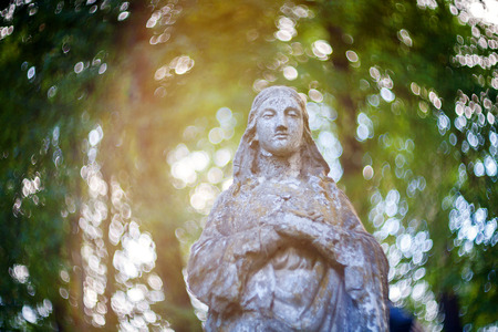 virgin: Statue of Virgin Mary at Rasu cemetery in Vilnius, Lithuania. Shot taken with a soft focus lens, shallow depth of field and lens flare Stock Photo