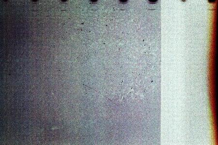 Blank grained film strip texture background with heavy grain, dust, scratches and light leak Foto de archivo