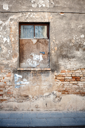Aged weathered street wall with a window Imagens