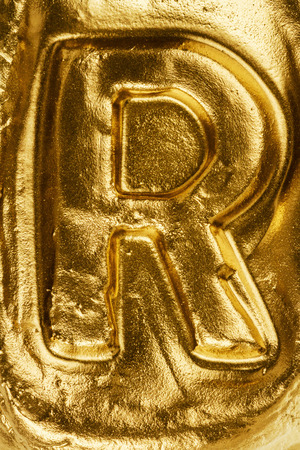 decorative letter: Beautiful handmade letter R on a shiny gold texture Stock Photo