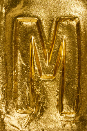 letter m: Beautiful handmade letter M on a shiny gold texture