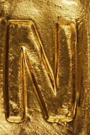 letter n: Beautiful handmade letter N on a shiny gold texture Stock Photo